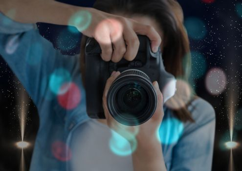 photographer foreground taking a photo with reflex camera. Blurred  blue and red lights overlap and