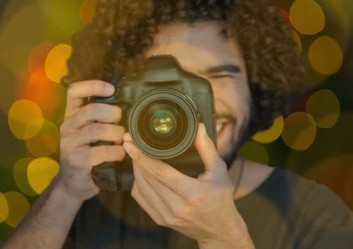 young photographer taking a photo ( foreground) with green and yellow bokeh background and overlap