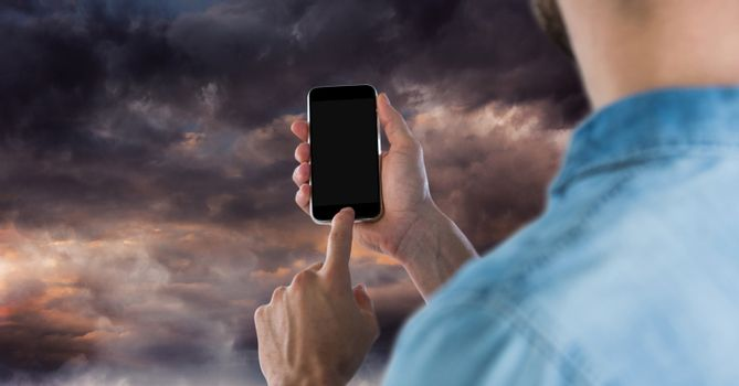 Part of a man using a mobile phone against darkness