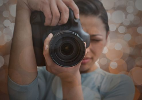 photographer foreground taking a photo with reflex. Blurred  brown lights background and overlap