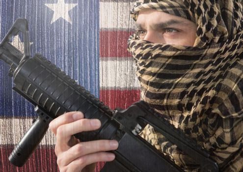 Soldier holding firearm against american flag