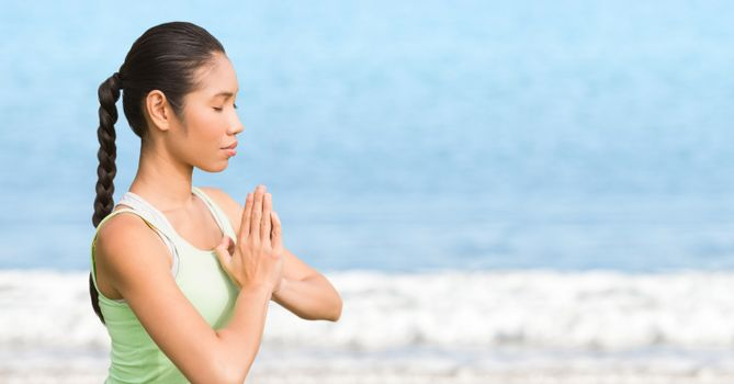 Woman meditating against blurry water