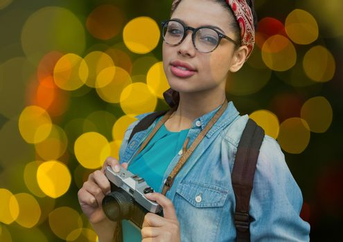 hipster photographer woman with glasses and vintage camera overlap with yellow, green and red blurre