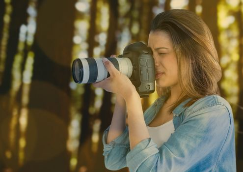 photographer taking a photo in the forest. Green and yellow bokeh overlap