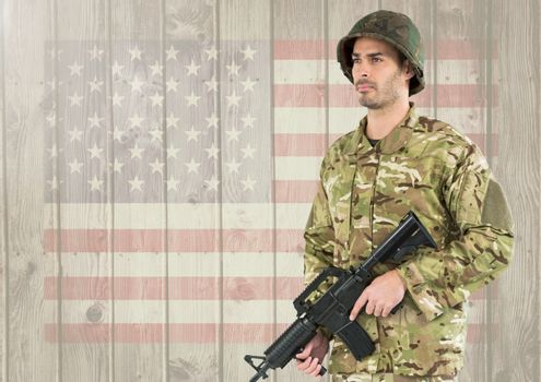 Proud soldier holding firearm against american flag