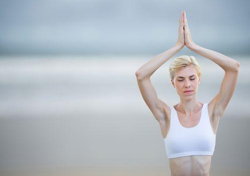 Woman meditating against blurry beach