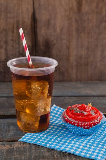 Decorated cupcake and cold drink with 4th july theme on wooden table