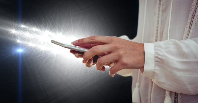 Part of a woman texting in darkness
