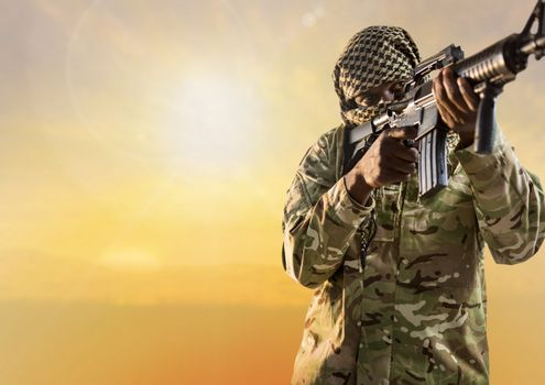 Black soldier holding a firearm in desert