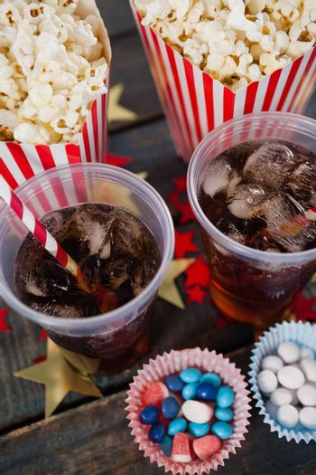 Popcorn, confectionery and drink arranged on wooden table
