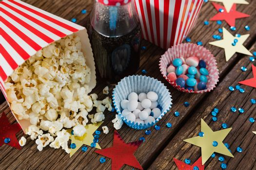 Scattered popcorn and sweet food decorated with 4th july theme on wooden table