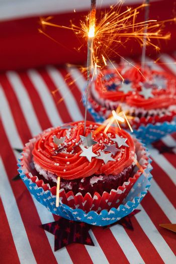 Burning sparkler on decorated cupcakes with 4th july theme