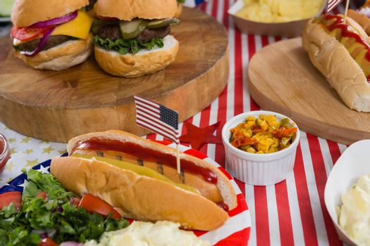 Close-up of burgers and hot dogs on wooden table with 4th july theme