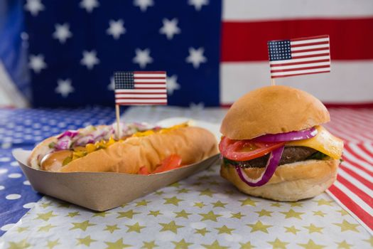 Close-up of burger and hot dog on wooden table with 4th july theme