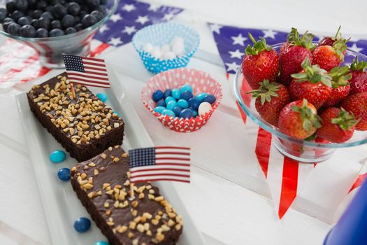 Close-up of sweet food and strawberries decorated with 4th july theme on wooden table