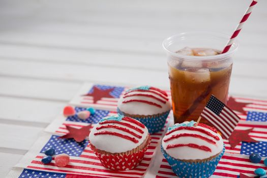 Decorated cupcakes and cold drink with 4th july theme on table