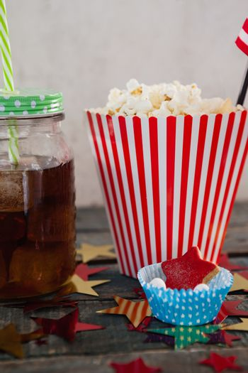 Popcorn, confectionery and drink with 4th july theme on wooden table