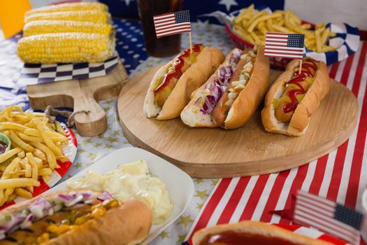 Close-up of burgers and corn cob on wooden table with 4th july theme