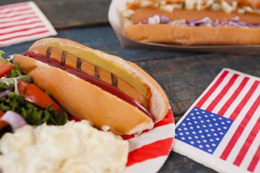 Close-up of hot dog with 4th july theme on wooden table