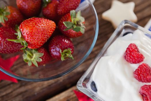 Close-up of strawberries in bowl with sweet food on wooden table