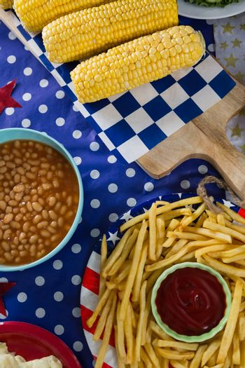 Close-up of french fries and corn cob on wooden table with 4th july theme