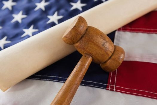 Close-up of gavel and rolled-up document arranged on American flag