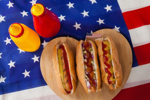 Close-up of hot dog on heart shape wooden board with 4th July theme