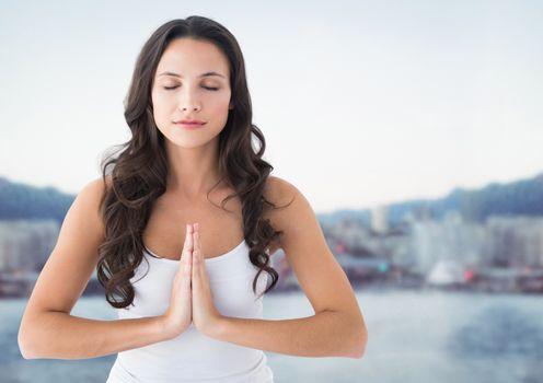 Woman meditating against blurry skyline