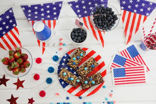 Sweet food and fruits decorated with 4th july theme on wooden table