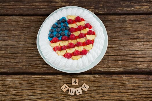 Overhead view of date blocks and fruitcake on wooden table with 4th july theme