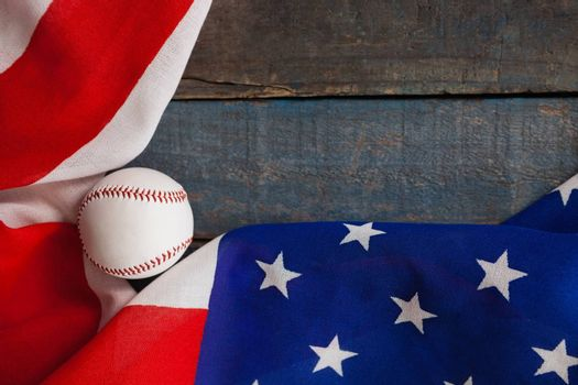 Overhead view of baseball and American flag on wooden table