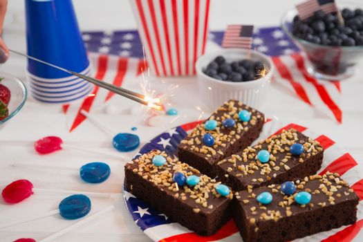 Close-up of sweet food and burning crackers decorated with 4th july theme on wooden table