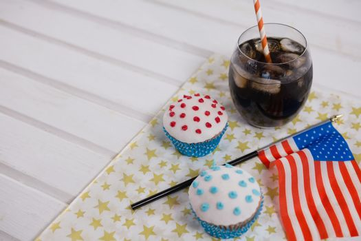 Close-up of drink and cupcake with 4th july theme on table