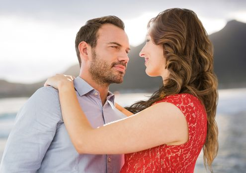 Couple dancing against blurry coastline
