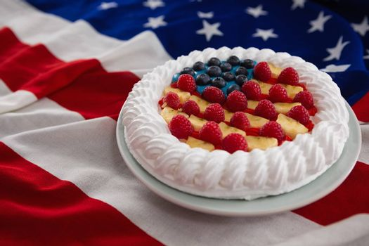 Close-up of fruitcake served in plate on American flag