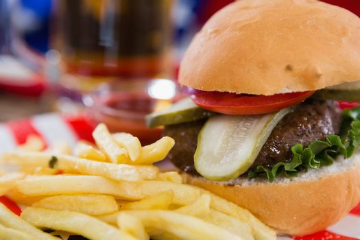 Close-up of burger and french fries on wooden table with 4th july theme