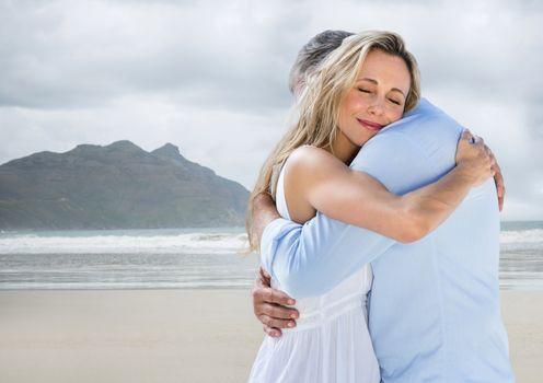 Couple hugging against blurry beach