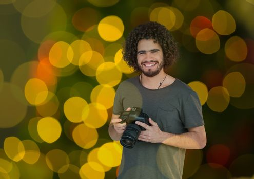 photographer with camera on hands. Green yellow and red bites bokeh background and overlap