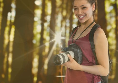 young happy photographer in the forest. With flares and bokeh overlap