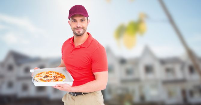 Delivery man with pizza against blurry housing estate