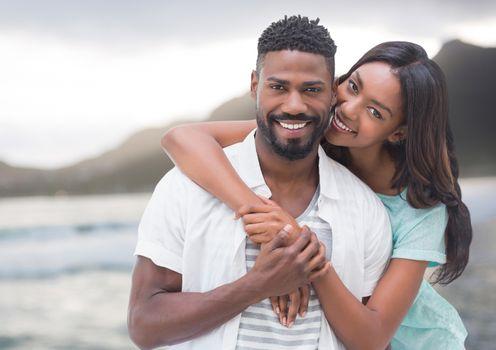 Couple embracing against blurry coastline