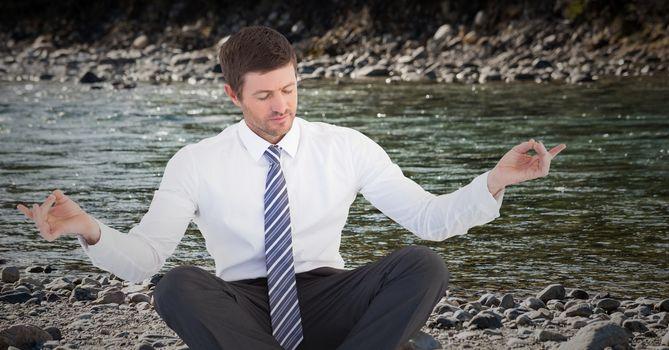 Business man meditating on riverbank