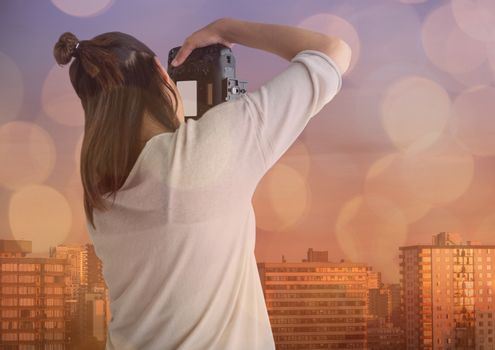 photographer taking a photo ( back) in front of the city. Blue and orange bokeh overlap