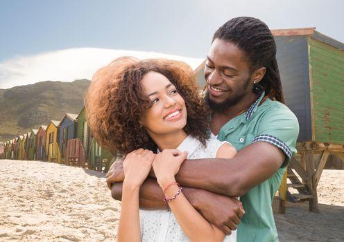 Millennial couple embracing against beach huts