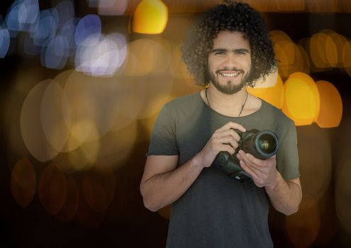 happy photographer with camera on hands at night. Blue and yellow blurred lights behind and overlap