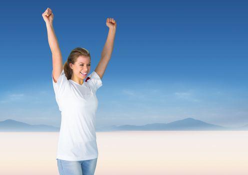 Woman cheering against blurry desert