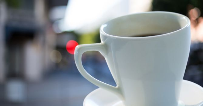 Coffee cup and saucer against blurry street