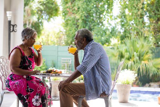 Senior couple having juice in yard