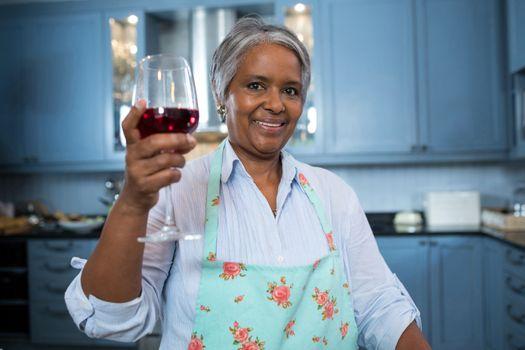 Portrait of woman showing wineglass