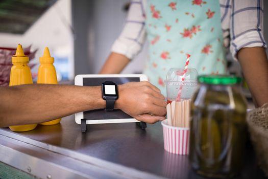 Man paying bill through smartwatch